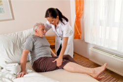caregiver assisting elderly man on getting out of bed