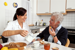caregiver preparing meal for an elderly patient